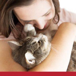 close up of woman cuddling a cat